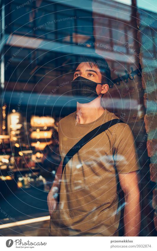 Junger Mann, der in einem Café an einer Ladenfront im Stadtzentrum steht und die Gesichtsmaske trägt, um eine Virusinfektion zu vermeiden Kaukasier Gespräch