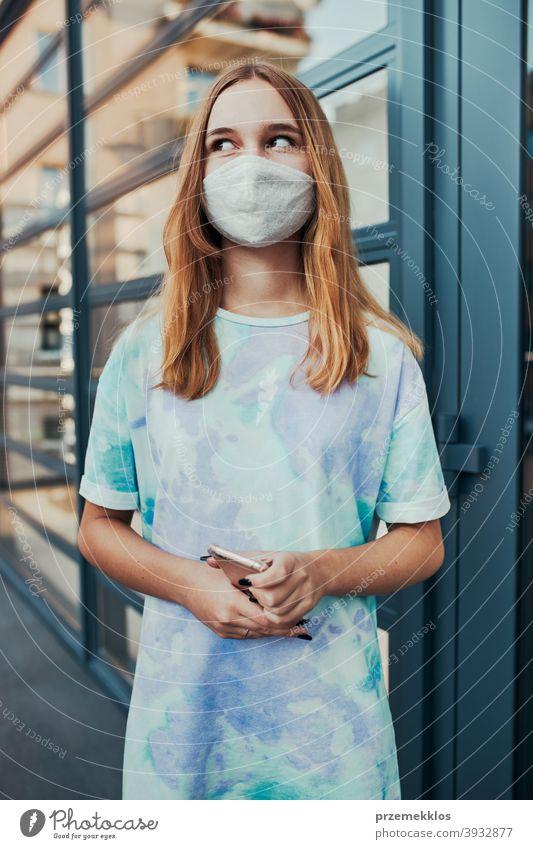Porträt einer jungen Frau, die an der Ladenfront in der Innenstadt steht und eine Gesichtsmaske trägt, um eine Virusinfektion zu vermeiden Kaukasier Funktelefon
