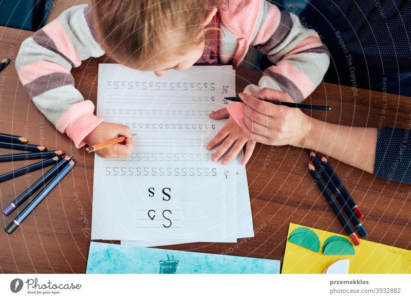 Kleines Mädchen im Vorschulalter, das mit Hilfe seiner Mutter lernt, Briefe zu schreiben Aufmerksamkeit Kaukasier Kind Kindheit niedlich Bildung lehrreich Spaß