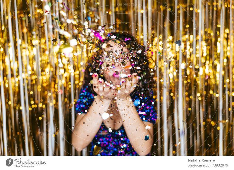 Selektiver Fokus. Eine Frau in einem eleganten glänzenden Kleid und Weihnachtsdekorationen hinter ihr bläst etwas Konfetti in die Kamera. Silvester Party Konzept