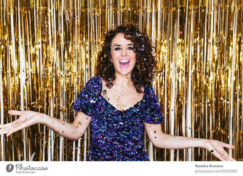 Eine schöne Frau in eleganter Kleidung mit Weihnachtsdekorationen hinter ihr feiern Silvester, während einige Konfetti über sie fällt. Silvesterparty zu Hause Konzept