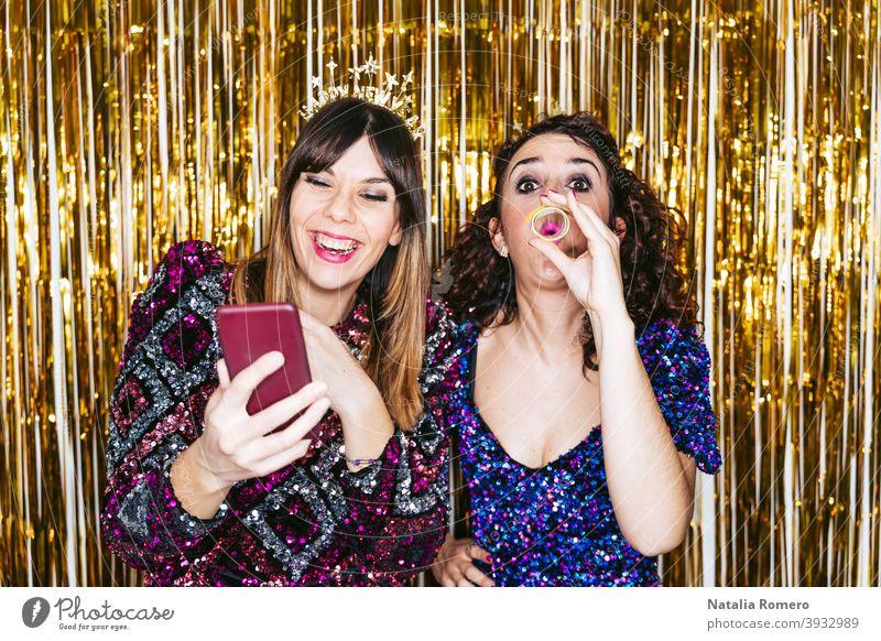 Zwei schöne Frauen mit Party-Kleidung und Weihnachten Stirnbänder haben Spaß zusammen in einer Silvesterparty mit einigen Porträts von ihnen. Silvester Konzept