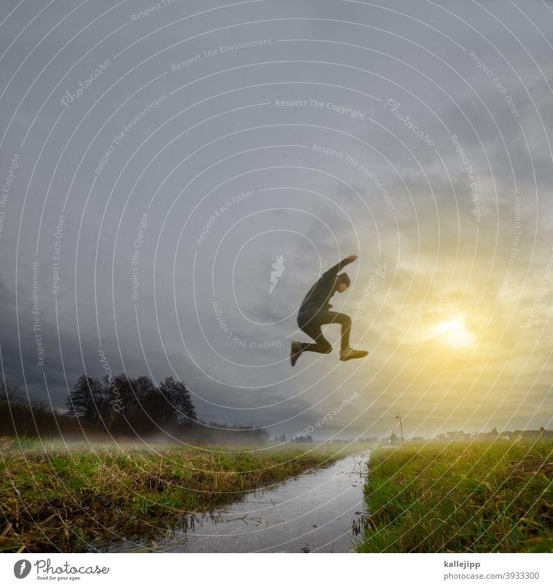 alt gegen neu springen sprung Freude Mann Sport Wasser Wiese Bach Natur Nebel Nebelschleier Himmel Wolken Außenaufnahme Farbfoto fliegen Aktion Licht Landschaft