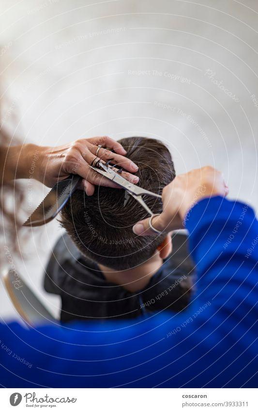 Lustiger Junge bekommt Haarschnitt zu Hause mit Schere bezaubernd Friseur Barbershop Schönheit Kaukasier Kind Kindheit schließen Kamm geschnitten niedlich Gerät