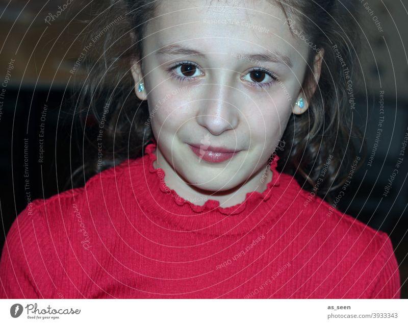 Mädchen in rotem Pullover 8-13 Jahre braune Haare braune Augen direkter Blick Lächeln selbstbewusst fröhlich angeblitzt Porträt schön Mensch Farbfoto feminin