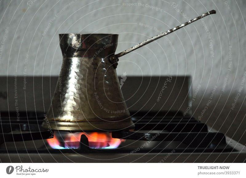 Türkische Espresso Kanne aus gehämmertem Metall steht zur Kaffee Zubereitung auf der Gasflamme des Küchenherdes türkisch Kaffee trinken Kaffee kochen
