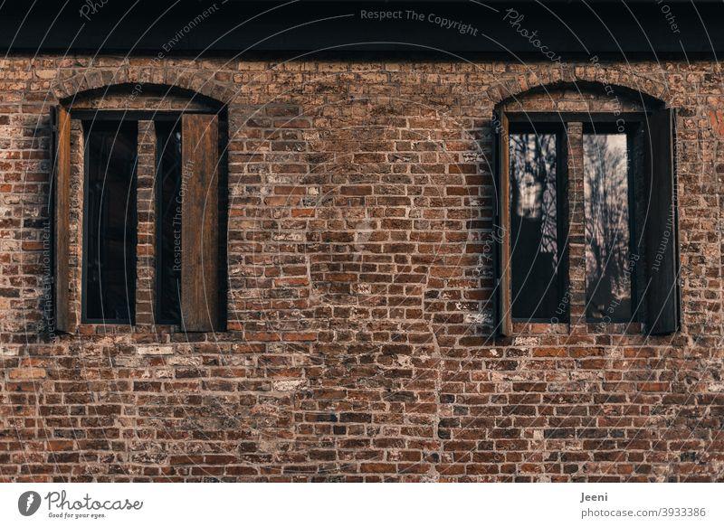 Schöne alte Backsteinwand mit symmetrischen Fenstern und Fensterläden aus Holz Backsteinfassade Backsteinhaus Backsteinmauer Backsteine Haus Gebäude Gebäudeteil