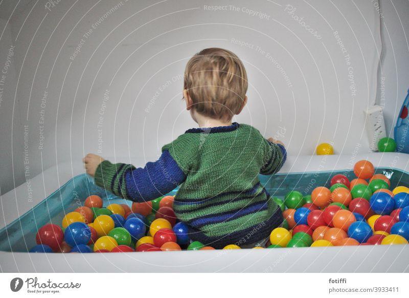 Kind im Bällebad Spielen Spielzeug Ball reichhaltigkeit versunken bunt Kleinkind vertieft rund Kindheit Freude Mensch Glück Aktion Pool Rückansicht