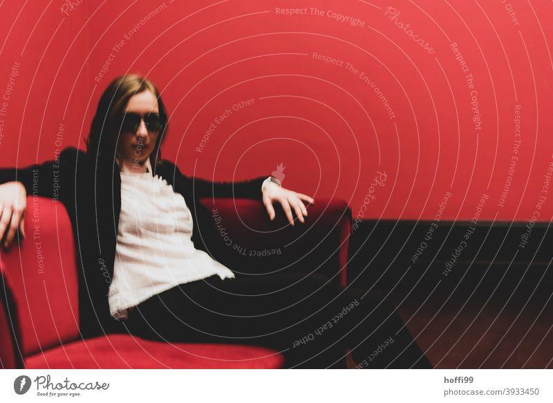 die Frau mit Sonnenbrille auf dem roten Sofa blickt in die Kamera - das Rot um sie rum ist ganz schön rot ... Gesicht verschwommen Junge Frau