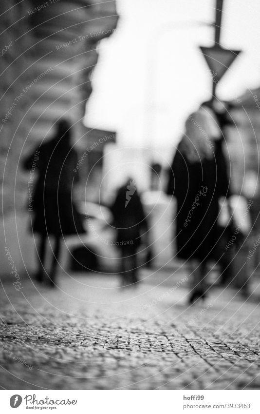 verschwommene Passanten auf einem gepflasterten Fussweg Bürgersteig Tristesse unscharfer Hintergrund Menschen Menschengruppe Pflastersteine Pflasterweg