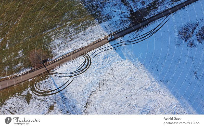 Drohnenfoto von einem weißen Auto, das im Winter auf einer Straße vom Licht in den Schatten fährt luftaufnahme drohnenfoto auto winter straße fahren schnee