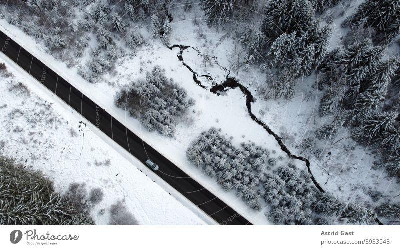 Luftaufnahme mit einer Drohne von einer Straße mit einem Auto das im Winter durch den Wald fährt luftaufnahme drohnenfoto auto winter straße fahren schnee wald