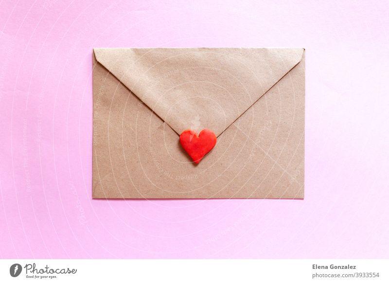 Liebesbrief in einem Bastelumschlag mit lehmrotem Herz auf rosa Hintergrund. Kuvert Handwerk Bastelpapier Symbole Post Urelemente Ideen Partnerschaft Details