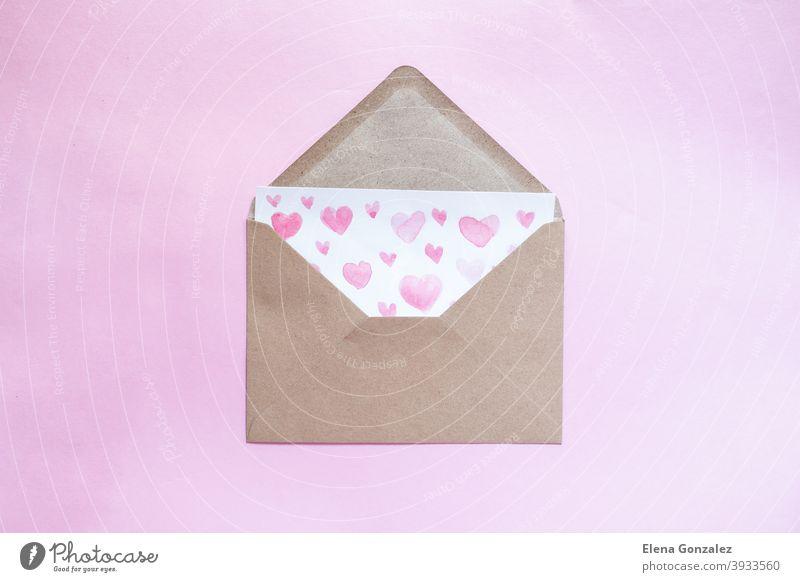 Liebesbrief mit Wasserfarbe rosa Herzen in einem Handwerk Umschlag auf rosa Hintergrund. Kuvert Bastelpapier Symbole Post Urelemente Ideen Partnerschaft Details