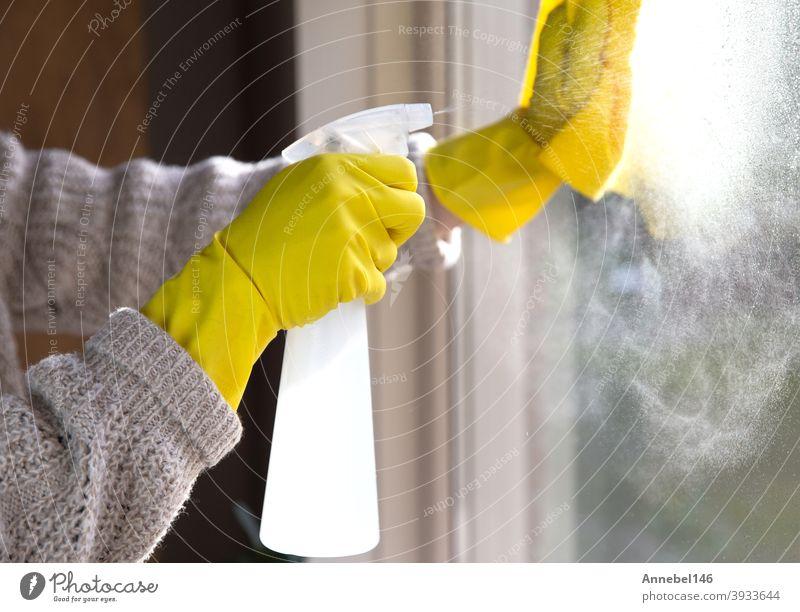 Reinigung eines Fensters mit Sprühwaschmittel, gelben Gummihandschuhen und Geschirrtuch auf Arbeitsfläche Konzept für Hygiene, Business und Gesundheit Konzept