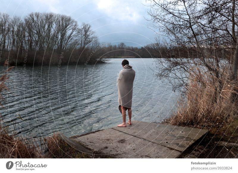 Junger Mann, im Winter nackt in eine Decke gehüllt, blickt auf einen See Eisschwimmen Winterbaden eisbaden gesund Wintertag junger Mann kältegefühl Rückansicht
