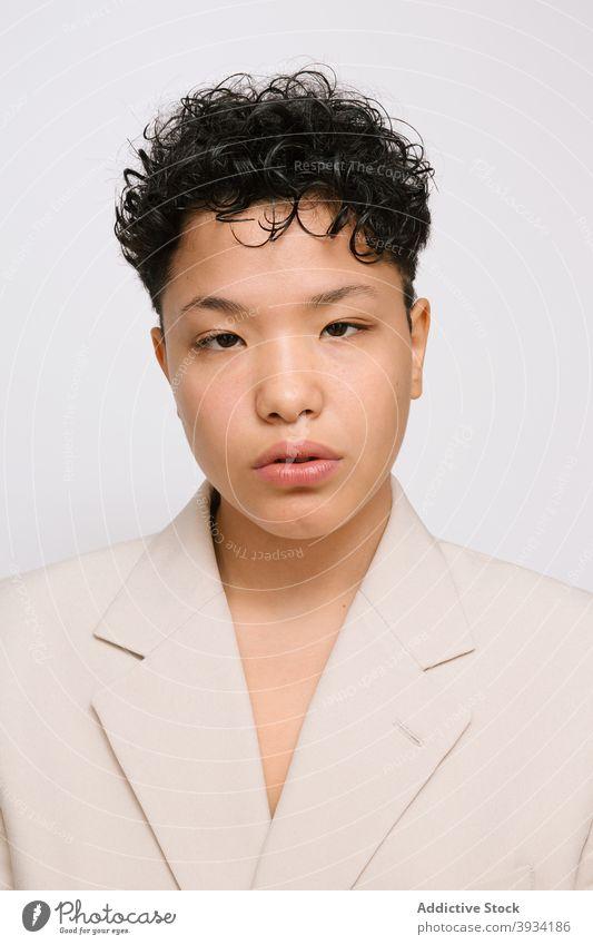 Junge Latina-Frau mit asiatischen Augen, trägt einen beigen Blazer Schönheit jung lateinamerikanisch Vielfalt multikulturell Porträt natürliche Schönheit Haut
