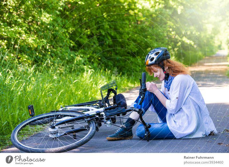 eine Frau hatte einen Unfall, sie ist mit einem Fahrrad gestürzt und hat sich verletzt Fahrradunfall Sturz Verletzung Fahrradfahrer Helm Knie Strasse Weg Sommer