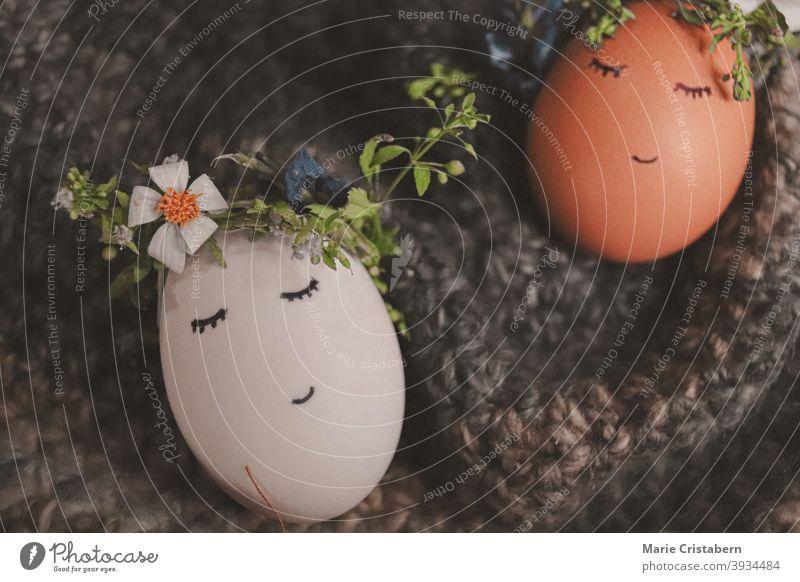 Niedliche Eier mit Blumenkränzen und gezeichneten Gesichtern als Dekoration für Ostern und den kommenden Frühling österliche Dekoration Ostereier