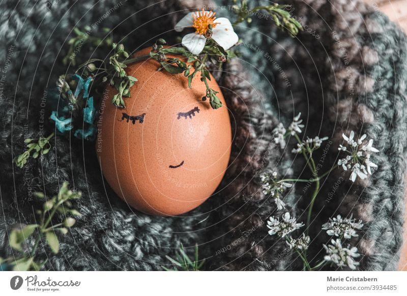 Nahaufnahme eines Eies mit einer Blumenkrone als Dekoration und Symbol für Ostern und das Kommen der Frühlingssaison Osterei Osterurlaub niedlich April März