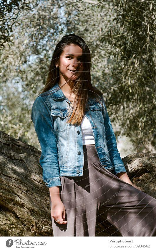 Schöne langhaarige Teenager-Frau mit braunen Haaren lehnt an einem Baum Lehnen grün Natur brünett Gras Kofferraum lässig Landschaft Jeansstoff Grasland