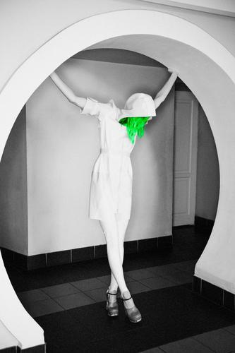 Grüne Haare - egal. Auch wenn das ganze Bild schwarz-weiß ist. Latex-Mode-Fotoshooting mit einem weiblichen Model mit enorm langen Beinen in High Heels und einem weißen Regenmantel mit Kapuzenpulli.