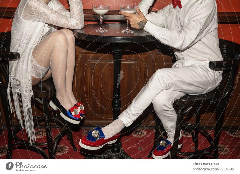 Es ist ein Date und die beiden jungen Leute flirten über den ganzen Tisch. Ganz in Weiß gekleidet und mit avantgardistischen Schuhen, die schon von weitem glänzen, trinken sie ein Glas Milch. Der rote Teppich repräsentiert dieses schicke Restaurant als perfekten Ort zum Flirten.