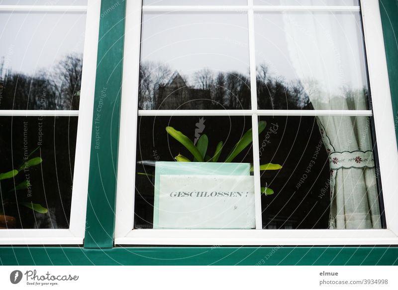 """Hinter der Glasscheibe des Fensters einer Gaststätte steht auf einem Blatt Papier in großen Druckbuchstaben """"GESCHLOSSEN"""" / Coronakrise / Prävention geschlossen"""
