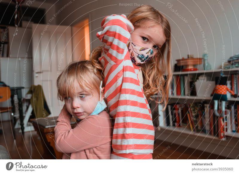 Geschwister Schwestern posieren Rücken an Rücken Stoffmaske Kind Mundschutz Kinder Frau Mädchen im Innenbereich heimwärts zu Hause Kaukasier Gesichtsmaske