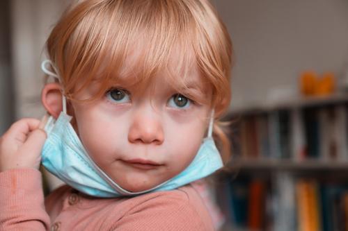Kind mit Gesichtsmaske unter dem Kinn Mundschutz Frau Mädchen im Innenbereich heimwärts zu Hause Kaukasier schützend 2020 Sperrung Quarantäne reales Leben