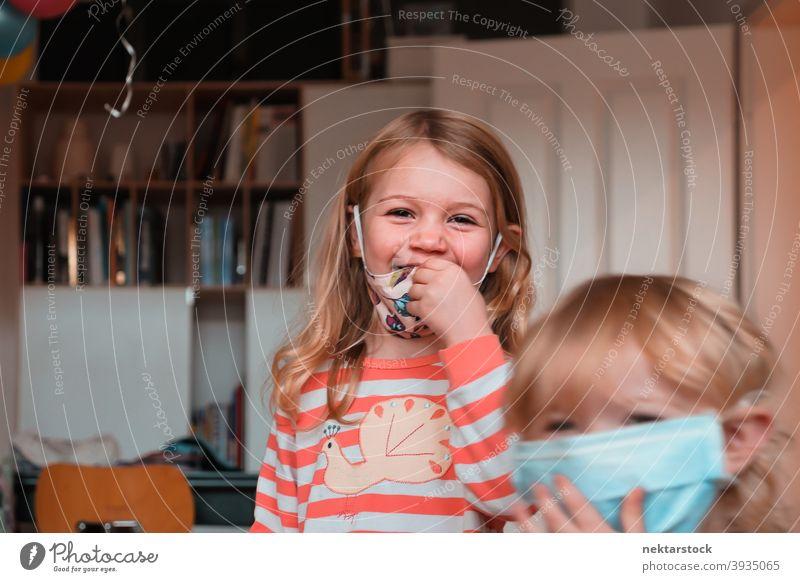 Geschwister lächelnd mit Gesichtsmasken Mundschutz Kind Schwestern Kinder Frau Mädchen im Innenbereich heimwärts zu Hause Rücken an Rücken Kaukasier schützend