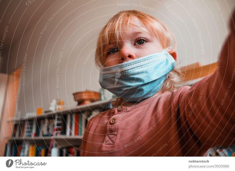 Zwei Jahre altes Mädchen mit Gesichtsmaske in Innenräumen Mundschutz Kind Frau im Innenbereich heimwärts zu Hause Kaukasier schützend 2020 Sperrung Quarantäne
