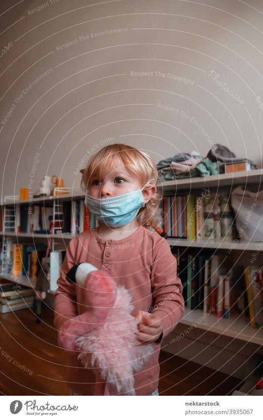 Kind trägt Gesichtsmaske zu Hause Mundschutz Frau Mädchen im Innenbereich heimwärts Kaukasier schützend 2020 Sperrung Quarantäne reales Leben echte Menschen