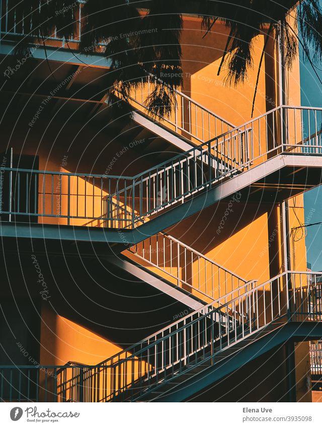 Buntes Treppenhaus mit gelber Wand an einem sonnigen Tag. Tapete eines Gebäudes mit Kopie Raum. Architektur Licht Großstadt Straße Textfreiraum Freitreppe