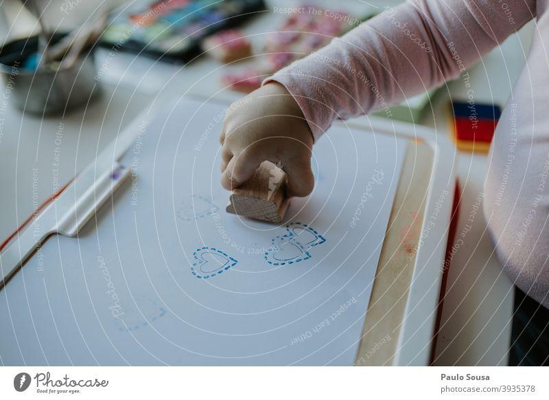 Close up Kind Hand spielen mit Briefmarken frankieren Kreativität Freizeit & Hobby Kindergarten malen Innenaufnahme Bildung Spielen Kindheit Farbfoto mehrfarbig