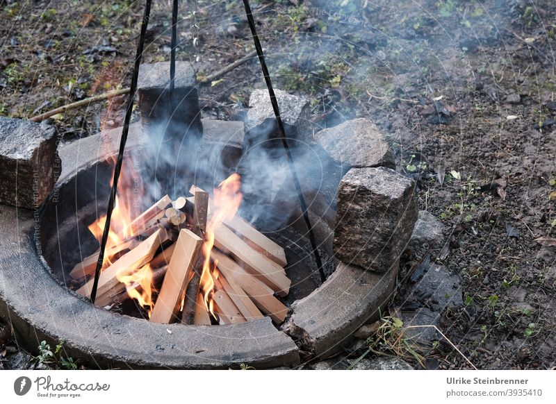 Anzünden eines Lagerfeuers zum Kochen Feuer Brennholz Holzscheite Kochfeuer Dreibein Feuer machen brennen Flammen anheizen entzünden heiß Feuerstelle Wärme