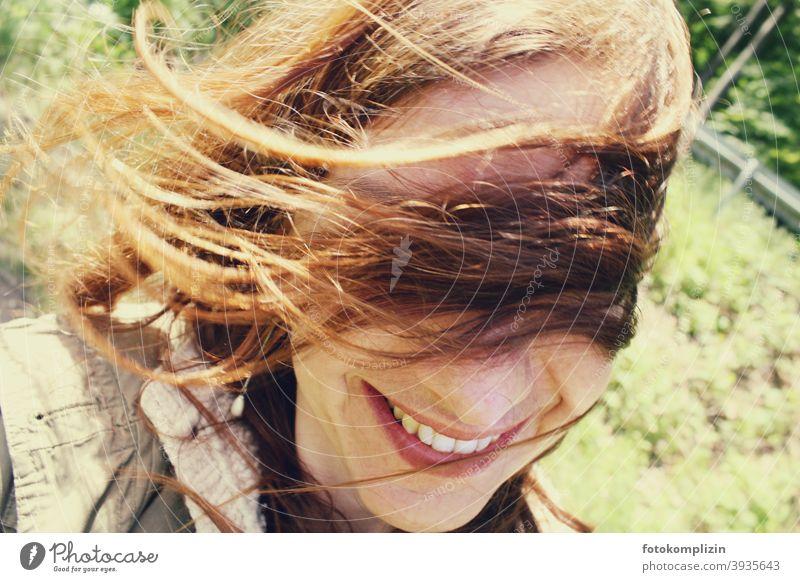 Portrait einer lächelnden Frau mit fliegenden Haaren vor den Augen Gesicht windig Identität blick portrait Porträt langhaarig natürlich lächelnde Frau Frisur