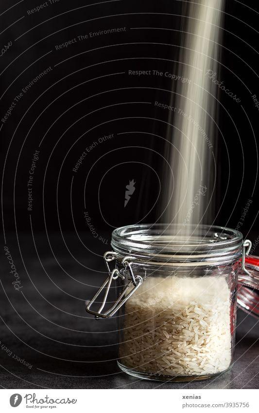In ein Vorratsglas mit Reis vor dunklem Hintergrund ergießt sich ein heller Strahl aus Reis von oben Glaswaren Ernährung Lebensmittel Lager plastikfrei