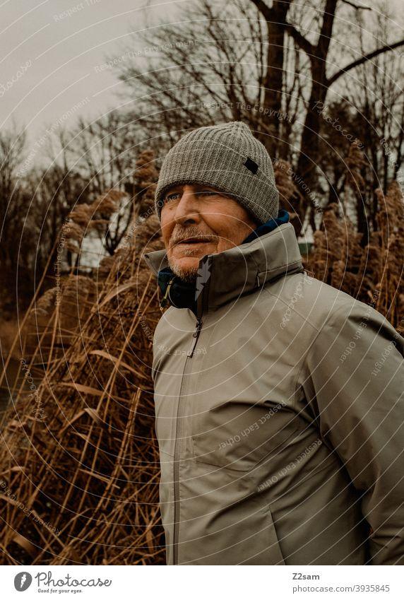 Portrait eines sportlichen Rentners in der Natur spazieren im Freien Sport rentner Ändern Mann Porträt mütze Winter Kälte Landschaft Wald sträucher freizeit