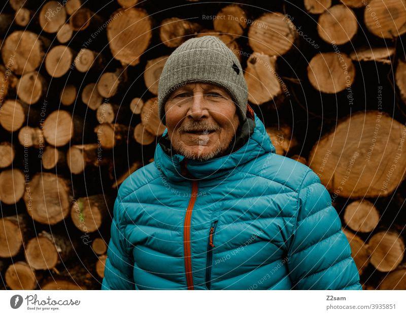 Porträt eines sportlichen Rentners vor einem Holzstapel spazieren Natur im Freien Sport rentner Ändern Mann mütze Winter Kälte Landschaft Wald sträucher Isar