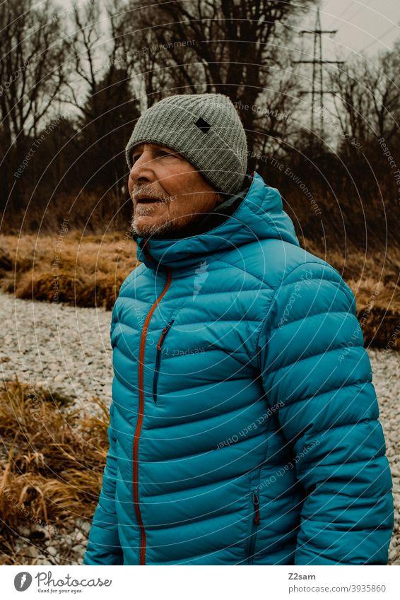 Portrait eines sportlichen Rentners in der Natur spazieren im Freien Sport rentner Ändern Mann Porträt mütze Winter Kälte Landschaft Wald sträucher Isar