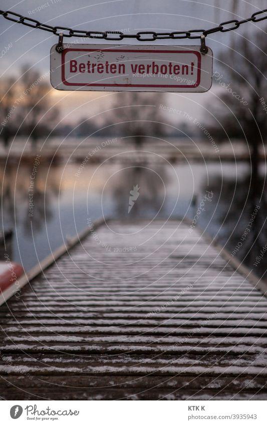Verschneiter Bootssteg und ein Betreten-Verboten-Schild Schilder & Markierungen Hinweisschild Warnhinweis Kette Absperrung Absperrkette Bäume Ufer Schnee Baum