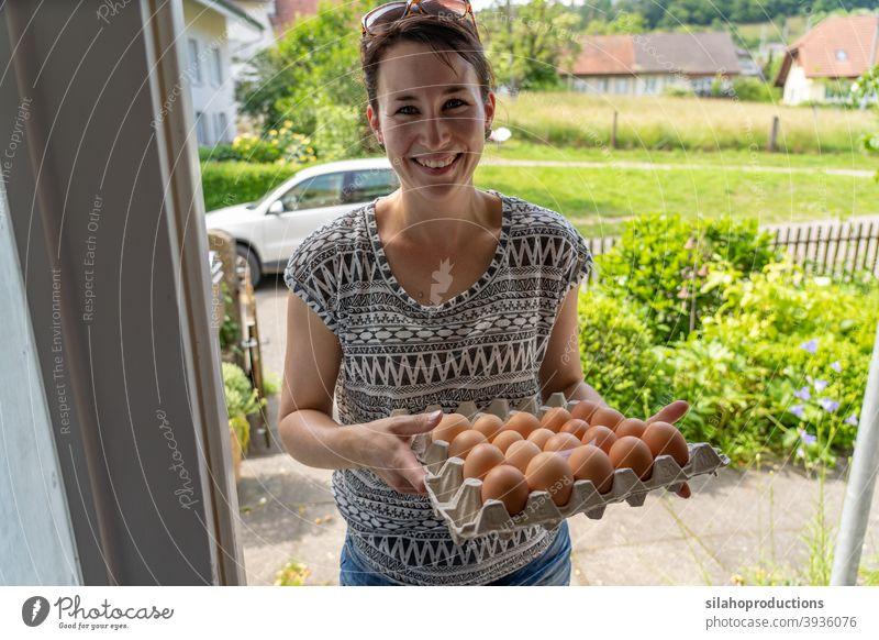 Lieferung von frischen Eiern an der Haustür durch eine junge lächelnde Frau. im Innenbereich Versand heimwärts Saison Dienst Ladung Arbeit Karton Kunde