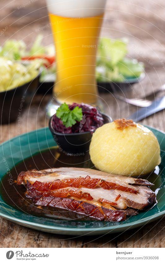 bayerischer Schweinebraten mit Knödeln rustikal Fett Dampf Schweinefleisch Braten Fleisch Teller Deutschland weiß Mittagessen Kloß Kartoffel Gericht geröstet
