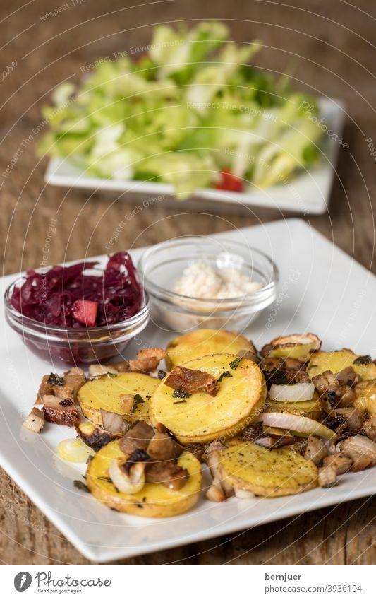 bayerisches Gröstl mit Salat auf Holz Kartoffel Schinken Zwiebel rustikal Kohl Meerrettich BLaukraut Rotkohl groestl geröstet Fleisch Füllung Pilze Mahlzeit
