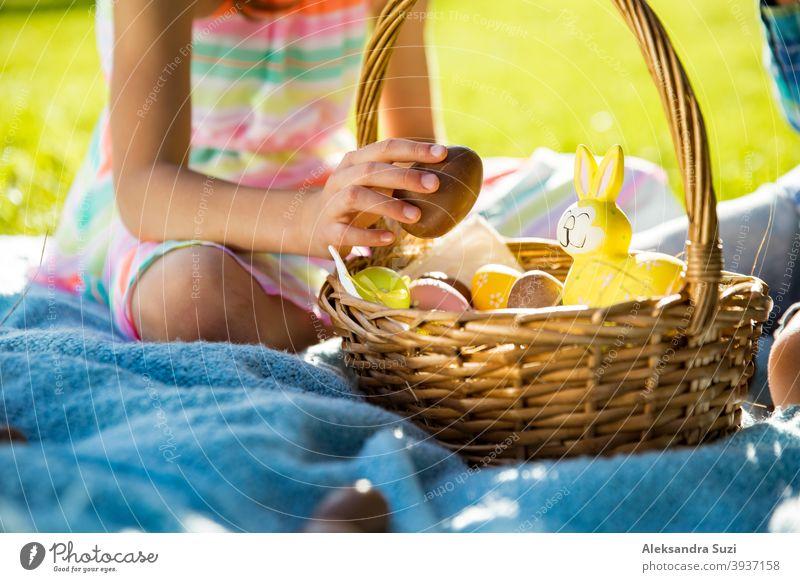 Netter Junge und Mädchen feiern Ostern, suchen und essen Schokoladeneier. Glückliche Familie Urlaub. Glückliche Kinder lachen, lächeln und Spaß haben. Schöner Frühling sonnigen Tag im Park