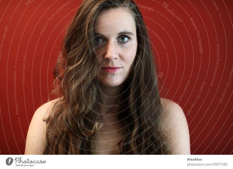 Porträt einer jungen Frau mit großen, grünen Augen vor einer roten Wand Junge Frau Zentralperspektive Erwartung Tag intensiv gesund authentisch Glück