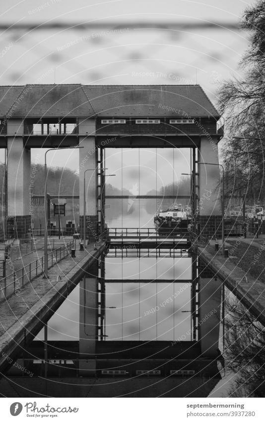 Schleusentor mit Wasser und Schiff im Hintergrund Herbst Dunst Schleusenanlage schwarz-weiß Menschenleer Außenaufnahme Lastkahn
