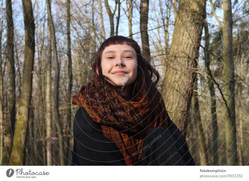 Porträt einer jungen lächelnden Frau mit Nasenpiercing unter kahlen Bäumen Junge Frau Frauengesicht verschmitzt weiblich junge Erwachsene brünett ponyfrisur
