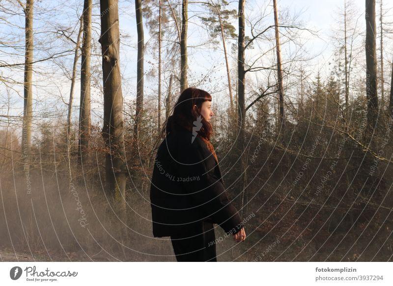 Junge Frau vor kahlen Bäumen junge Erwachsene Jugendliche Mädchen langhaarig blicken schauen weiblich Identität 18-30 Jahre Frühjahr brünett Wald Kälte